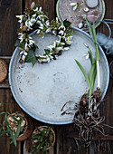 Heart-shaped wreath of snowdrops, ivy, and ivy berries on a metal tray