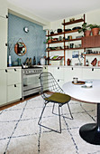 A wire chair at a dining table on a rug in an open-plan kitchen