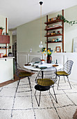 Wire chairs around a dining table on a rug in open-plan kitchen