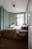 Doppelbett und Hocker als Beistelltisch im Schlafzimmer mit grüner Wand