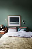 A picture above a double bed in a bedroom with a green wall