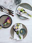 Tulips, hyacinths, daffodils, and grape hyacinths in small bouquets on plates
