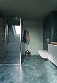 A shower cubicle in a bathroom with grey floor tiles
