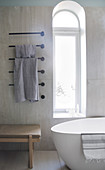 Free-standing bathtub in front of arched window