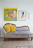 Pictures and a wall lamp above a grey day bed with cushions