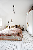 Boho style bedroom with a locker as a wardrobe and wooden floor