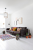 Colourful carpet in front of grey sofa with ethno cushions and picture gallery