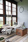 A wooden chest next to a day bed with blankets in a glass house