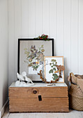 A collage of autumnal leaves in a picture frame and an acorn wreath on a wooden box