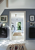 Hallway with grey-blue wall and view into the kitchen