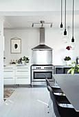 Blick neben Essbereich auf Küchenzeile mit Gasherd und Dunstabzugshaube