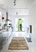 Teppichvorleger auf weißem Holzdielenboden vor Küchenzeile