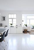 Blick neben Essbereich auf weißes Lowboard und Sitzbereich