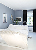 A double bed and black curtains in a blue-grey bedroom