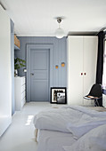 Double bed, black chair, white wardrobe and chest of drawers in blue-grey bedroom
