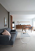 A grey upholstered sofa and a coffee table in a minimalist living area