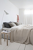 A double bed in a minimalist bedroom with white floorboards