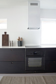 Kitchen unit with dark front, extractor bonnet next to window