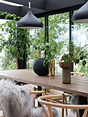 Self-made wooden dining table with classic chairs in the winter garden