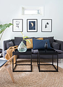 A grey upholstered sofa, a set of two coffee tables on a sisal carpet with art prints on the wall