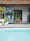 Blick über Pool durch geöffnete Schiebetür auf Stuhl im Wohnzimmer