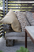 A rustic wooden bench with cushions on a terrace