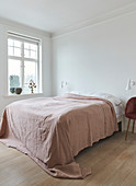 A double bed with a bedspread in a light bedroom