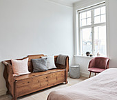 Rustic chest bench with pillows in a bright bedroom