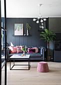 Dunkles Sofa mit Rosa Kissen vor dunkler Wand, Sitzpouf und Couchtisch im Vordergrund