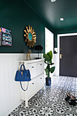 White shoe cabinet and sun mirror in the hallway with green wall and tiled floor