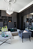 Dark living room wall, upholstered furniture, round coffee table and chandelier