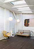 Armchair and sofa in a room with skylights and brick walls