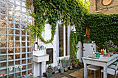 A table laid in a back garden with Virginia creeper growing against a wall