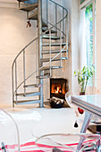 A corner fireplace under a metal spiral staircase