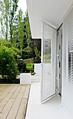 Open glass door with blinds leading to the terrace and the garden
