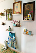 Pictures, vases and odds and ends on small shelves on the wall