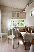 Antike Stühle und alte Bank am Tisch im Esszimmer mit Wandverkleidung