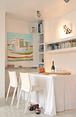 White chairs in front of a table with a tablecloth under built-in shelves