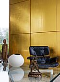 Goldene Wandpaneele im Wohnzimmer mit Designersessel