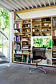 An office chair at a desk built into a bookcase