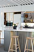 Barhocker an der Kücheninsel mit Edelstahlfront in moderner Küche