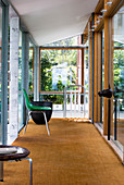 Green chair in a modern hallway with jute rug in a sun room