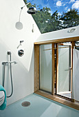 A shower in a bathroom with a glass roof and access to the garden