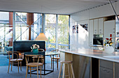 Bistro chairs at a round glass table in front of an open-plan kitchen