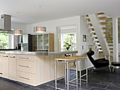 Kitchen island with a light front and stainless steel worktop, bar stool, and designer chair
