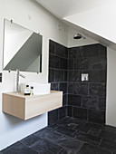 Simple vanity under mirror in white bathroom with anthracite-colored tiles