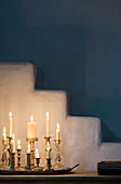 Group of candlesticks with burning white candles in front of plaster steps