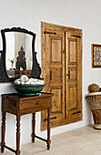 An antique side table and a mirror next to a wall cupboard with frame and panel doors