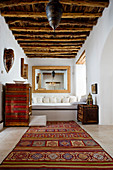 Oriental carpet in the rustic living room with wooden beam ceiling