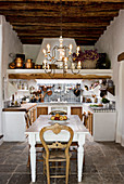 A chandelier above the dining table in a rustic open kitchen - dining room with a natural stone floor